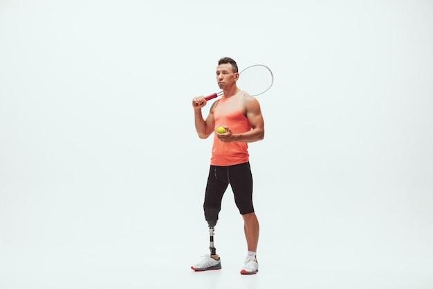 Athlet mit behinderungen oder amputierter isoliert auf weiß. professioneller männlicher tennisspieler mit beinprothesentraining Kostenlose Fotos