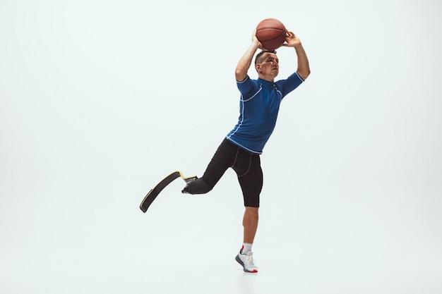 Athlet mit behinderungen oder amputierter isoliert auf weißem studioraum. professioneller männlicher basketballspieler mit beinprothesentraining und üben im studio. Kostenlose Fotos