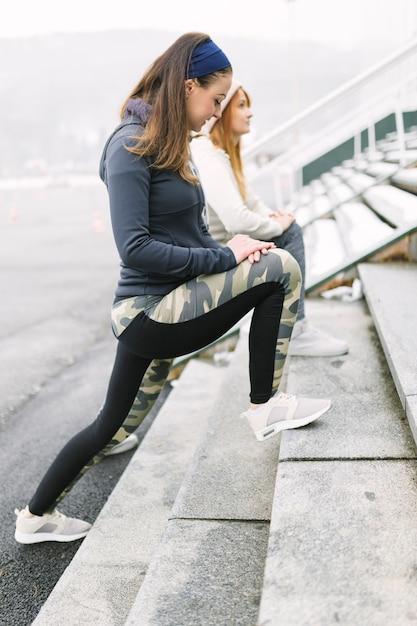 Athlet mit zwei frauen, der ihr bein auf schritten ausdehnt Kostenlose Fotos