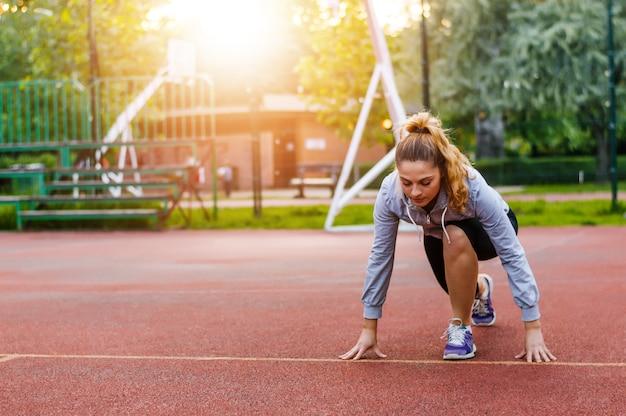 Athletische frau auf der laufbahn, die fertig wird, lauf zu beginnen. Premium Fotos