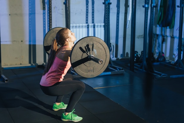 Athletische frau, die mit einem barbell in der turnhalle trainiert Premium Fotos