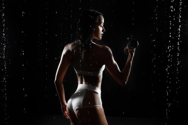 Athletische frau, die muskeln mit dummköpfen aufpumpt Premium Fotos