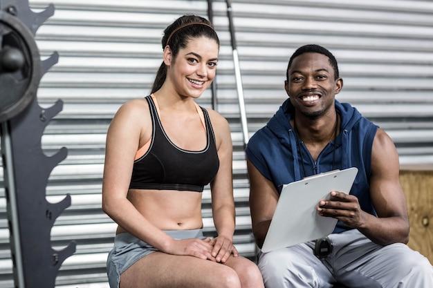 Athletische frau und trainer, die zur kamera an crossfit turnhalle lächelt Premium Fotos