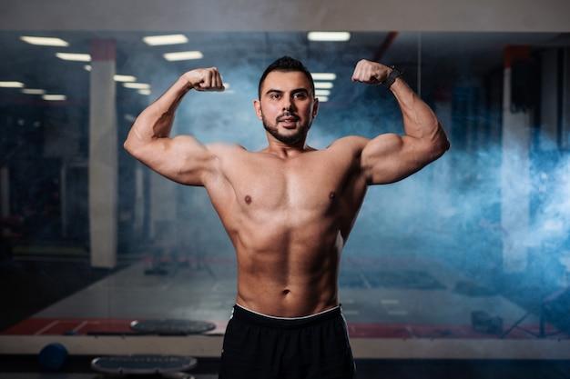 Athletische mannaufstellung, seine muskeln in der turnhalle vorführend Premium Fotos
