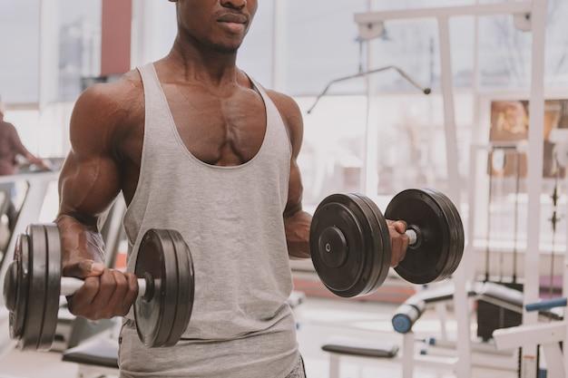 Athletischer afrikanischer mann, der mit dummköpfen an der turnhalle ausarbeitet Premium Fotos