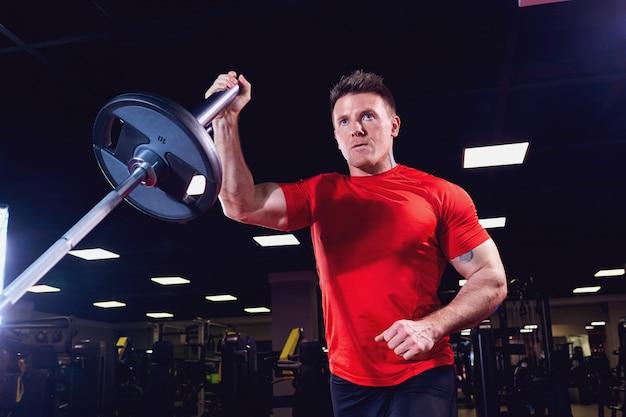 Athletischer männlicher athlet, der übungen mit einem barbell in der turnhalle tut Premium Fotos