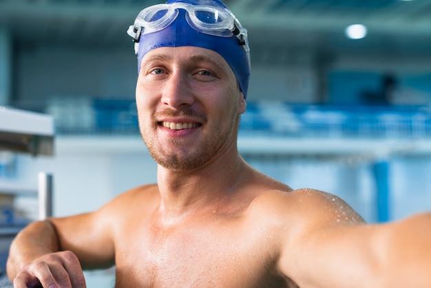 Athletischer männlicher schwimmer, der ein selfie nimmt Kostenlose Fotos