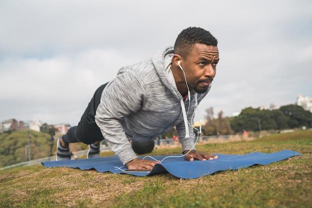 Athletischer mann, den das handeln drückt, ups. Premium Fotos