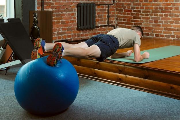 Athletischer mann, der balancierende übungen mit dem turnhallenball tut Premium Fotos