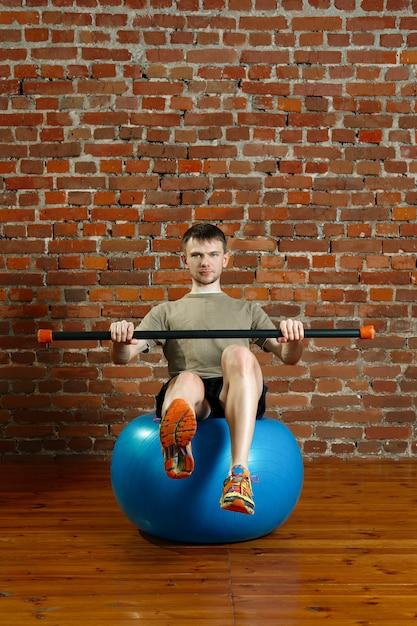 Athletischer mann, der balancierende übungen über dem turnhallenball mit gymnastischem stock tut Premium Fotos