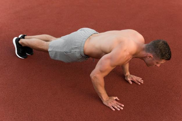 Athletischer mann, der liegestütze tut Kostenlose Fotos