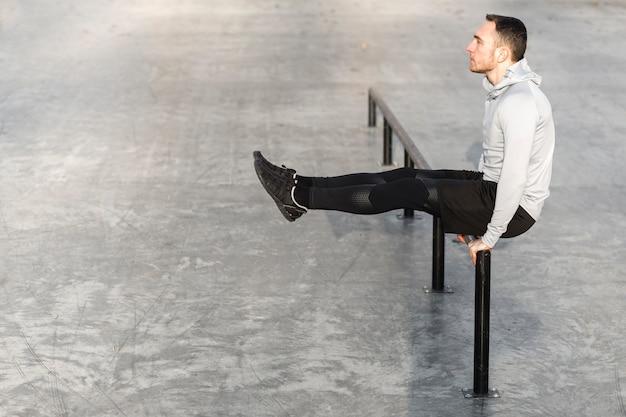 Athletischer mann der seitenansicht, der draußen ausarbeitet Kostenlose Fotos