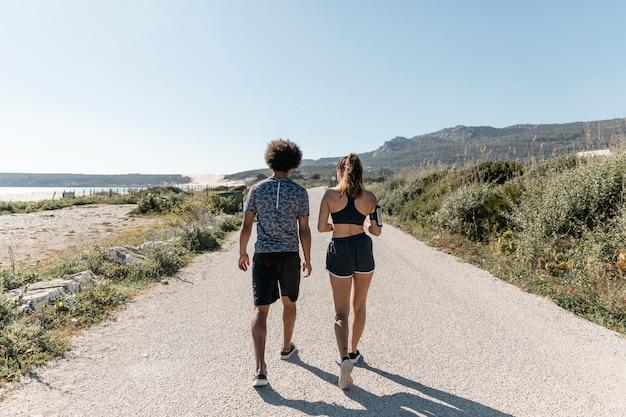 Athletischer mann und frau, die entlang straße gehen Kostenlose Fotos