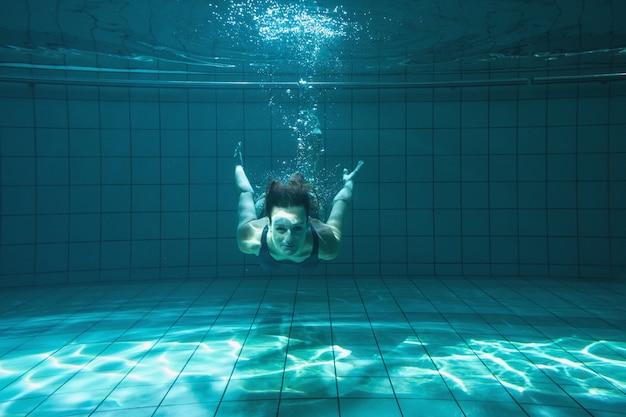 Athletischer schwimmer, der unter wasser an der kamera lächelt Premium Fotos