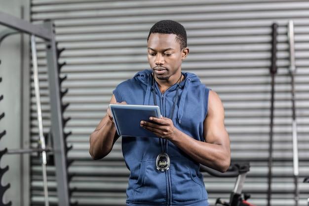 Athletischer trainer, der digitale tablette an crossfit turnhalle verwendet Premium Fotos