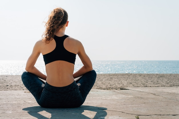 Athletisches mädchen mit dem gelockten haar in einem sport-bh, der morgens auf einem strand sitzt und meer betrachtet Premium Fotos