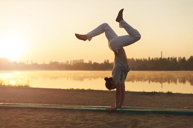 Athletisches yogamann-trainingstraining auf dem strandsonnenaufgang Kostenlose Fotos