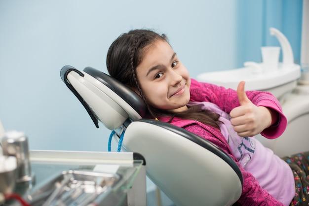 Atient mädchen, das sich daumen im zahnmedizinischen büro zeigt Premium Fotos