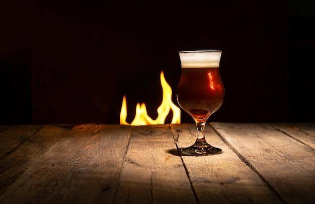 Atmosphärischer abend in einer kneipe. bierglas auf einem dunklen hölzernen hintergrund mit kamin Premium Fotos