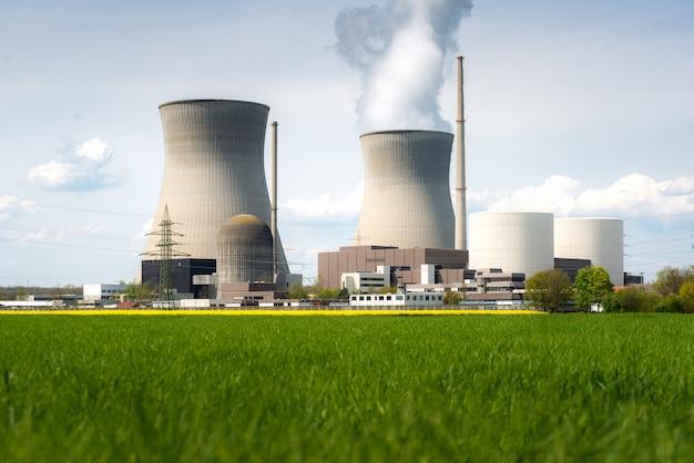 Atomkraftwerk mit gelbem feld und großen blauen wolken. Premium Fotos