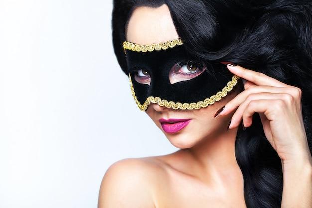 Atractive junge frau mit venedig-maskenstudioporträt. Premium Fotos
