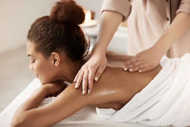Attraktive afrikanische frau, die massage entspannend im spa-salon hat. geschlossene augen. Kostenlose Fotos