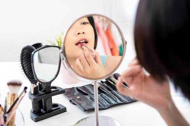 Attraktive asiatische frau, die roten lippenstift vor spiegel anwendet Premium Fotos