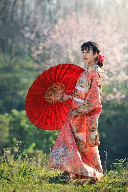 Attraktive asiatische frau, die traditionellen japanischen kimono mit rotem regenschirm trägt Premium Fotos