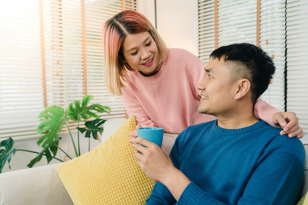 Attraktive asiatische süße paare genießen den liebesmoment, der warmen tasse kaffee oder tee in ihren händen trinkt Kostenlose Fotos