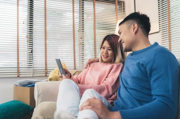 Attraktive asiatische süße paare unter verwendung der tablette beim lügen auf dem sofa, wenn in ihrem wohnzimmer sich entspannen Kostenlose Fotos