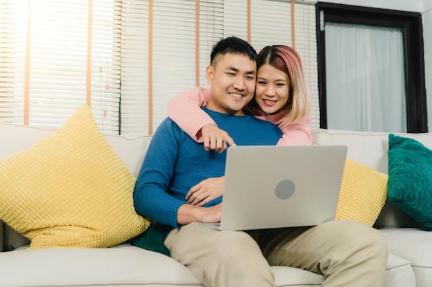 Attraktive asiatische süße paare unter verwendung des computers oder des laptops beim auf dem sofa liegen, wenn sie sich entspannen Kostenlose Fotos