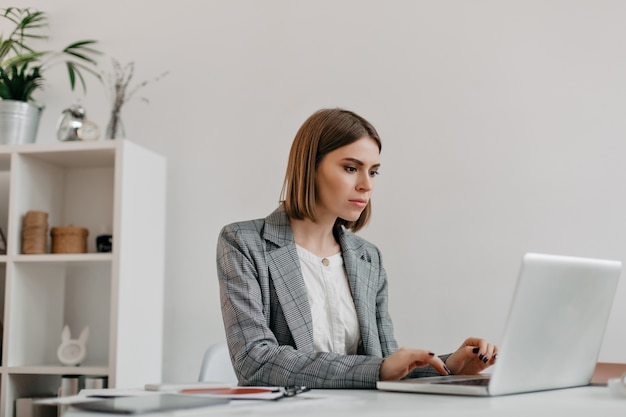 Attraktive blonde frau, die brief in laptop an ihrem arbeitsplatz schreibt. porträt der dame in der stilvollen jacke im hellen büro. Kostenlose Fotos