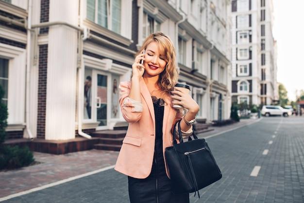 Attraktive blonde frau mit langen haaren, die in der korallenjacke auf straße gehen. sie telefoniert, hält eine tasse in der hand und lächelt nach unten. Kostenlose Fotos