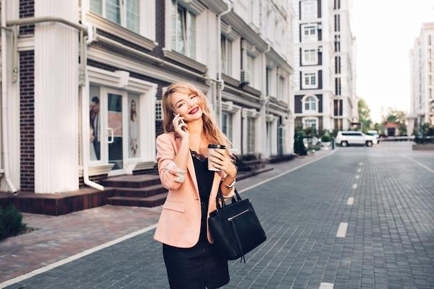 Attraktive blonde frau mit langen haaren geht durch britisches viertel. sie trägt ein schwarzes kleid, hält kaffee und telefoniert Kostenlose Fotos