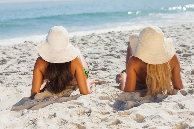 Attraktive blondine und brunette in den bikinis, die auf dem sand liegen Premium Fotos