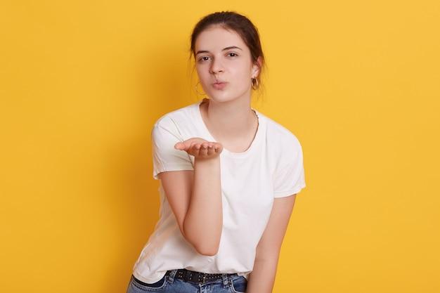 Attraktive dunkelhaarige junge frau kleidet weißes t-shirt, das luftkuss beim posieren bläst Kostenlose Fotos