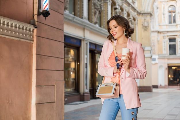 Attraktive elegante frau im stilvollen outfit, das in der stadt, straßenmode, frühlingssommertrend, lächelnde glückliche stimmung geht, rosa jacke und bluse, accessoires, fashionista beim einkaufen in italien trägt Kostenlose Fotos