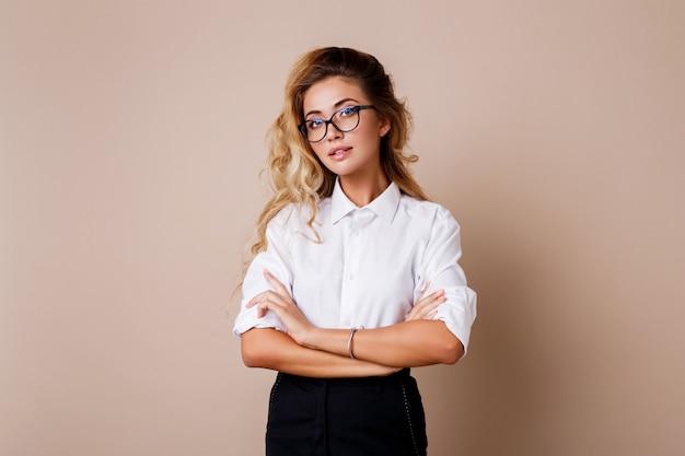 Attraktive erfolgreiche geschäftsfrau mit offenem lächeln suchen. lehrer oder angestellter. beige wand. Kostenlose Fotos