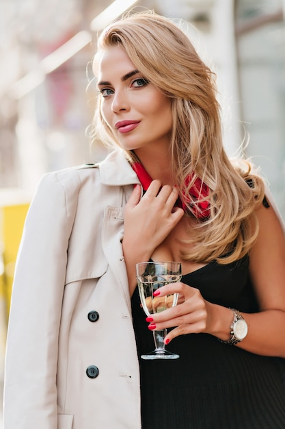Attraktive europäische frau mit weinglas trägt beige mantel sanft lächelnd. spektakuläre blonde dame im schwarzen kleid und in der silbernen armbanduhr, die mit vergnügen auf ereignis aufwirft. Kostenlose Fotos