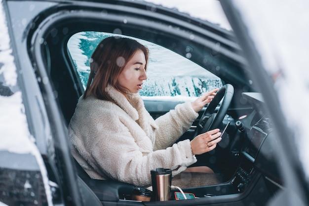 Attraktive fahrerin, die hinter dem lenkrad in ihrem auto sitzt Kostenlose Fotos
