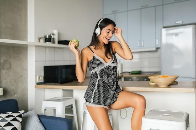 Attraktive frau der jungen brünetten, die in der küche am morgen kocht, grünen apfel isst, lächelt, glückliche stimmung, positive hausfrau, gesunden lebensstil, musik auf kopfhörern hört, beißt Kostenlose Fotos