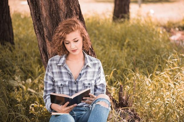 Attraktive frau, die auf baum- und lesebuch sich lehnt Kostenlose Fotos
