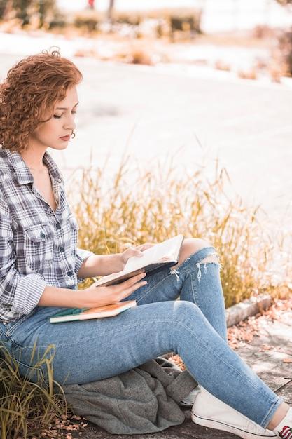 Attraktive frau, die auf gras und lesebuch sitzt Kostenlose Fotos