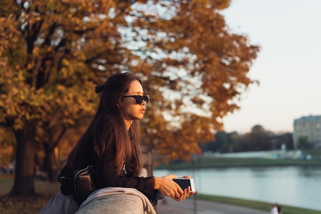 Attraktive frau, die draußen smartphone im park verwendet Kostenlose Fotos