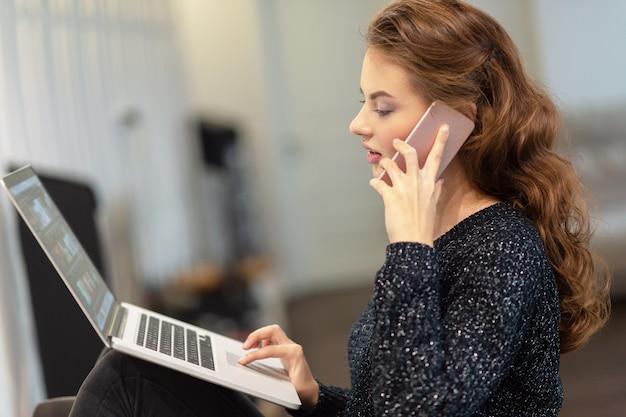 Attraktive frau, die durch das smartphone anruft, das am computer arbeitet. junge frau mit handy und laptop. Kostenlose Fotos