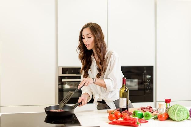 Attraktive frau, die fleisch auf der wanne mit wein und gemüse in der küche brät Premium Fotos