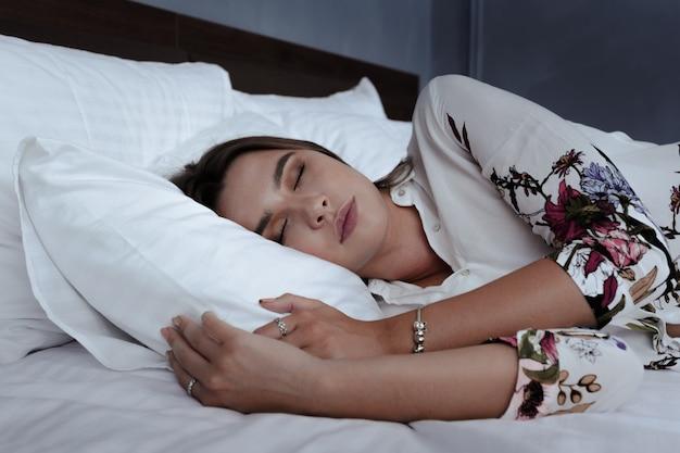 Attraktive frau, die im bett im hotelzimmer schläft Premium Fotos