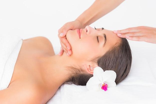 Attraktive frau, die kopfmassage in der badekurortmitte empfängt Premium Fotos