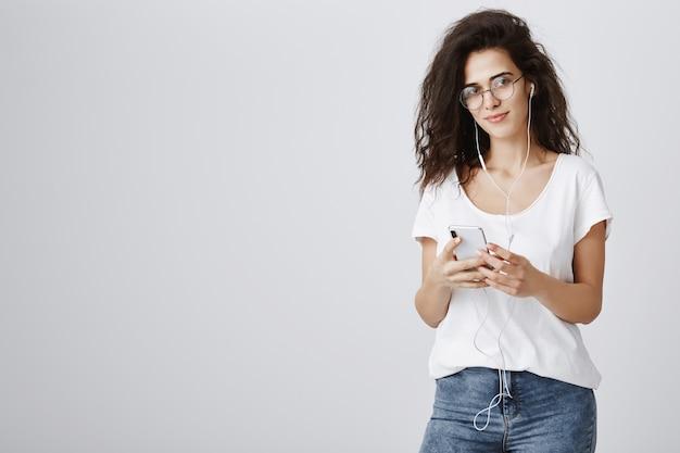 Attraktive frau, die musik in kopfhörern und nachrichten über mobiltelefon hört Kostenlose Fotos