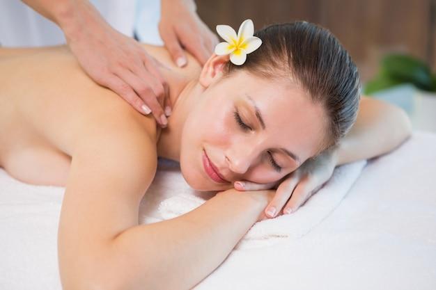 Attraktive frau, die rückenmassage in der badekurortmitte empfängt Premium Fotos